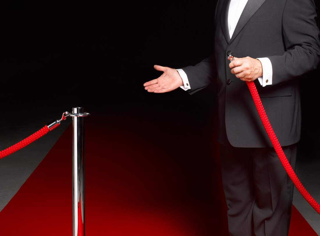 Man opening velvet rope to let you in