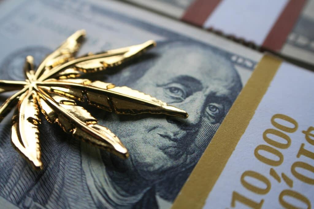 gold cannabis leaf on us dollar bill